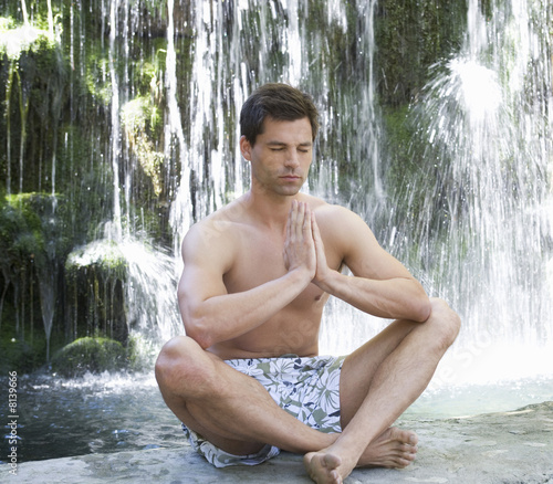 A man meditating by a waterfall