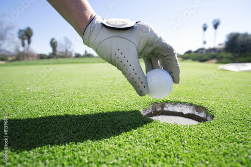 Person taking golf ball out of hole on putting green, close-up, side view, focus on hand and golf glove
