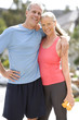 Active senior couple, in sportswear, standing with arms around each other on driveway, woman holding dumbbell weights, smiling, portrait