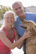 Active senior couple, in sportswear, stroking golden retriever, smiling, portrait