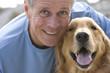 Active senior man, in blue t-shirt, crouching beside golden retriever, smiling, close-up, front view, portrait