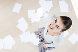 Woman smiling with dropped paperwork on the floor, aerial shot