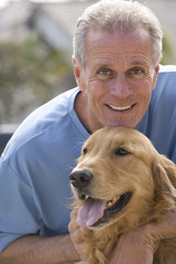 Active senior man, in blue t-shirt, crouching beside golden retriever, smiling, close-up, front view, portrait