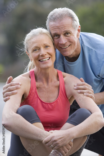 Active senior couple, in sportswear, resting on driveway, man embracing woman, smiling, front view, portrait