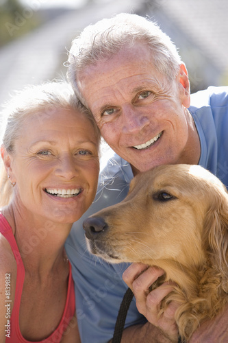 Active senior couple, in sportswear, stroking golden retriever, smiling, close-up, portrait