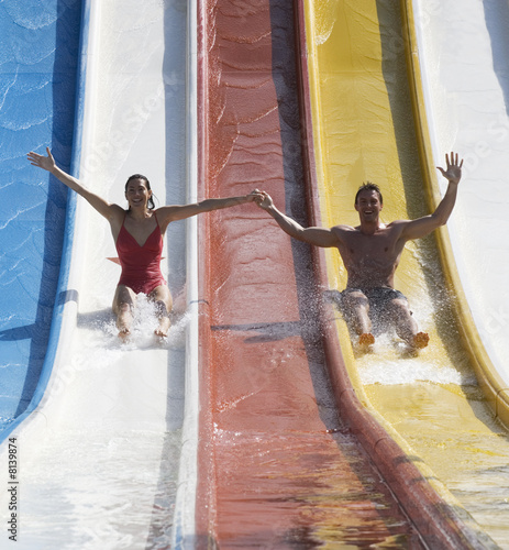 A couple coming down a slide in a waterpark