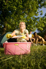 Friends sitting near tent in woodland clearing, focus on young woman kneeling beside pink bowl, washing plates, smiling, portrait (surface level)