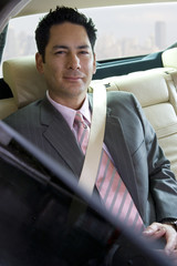 Businessman sitting in backseat of car, wearing seatbelt, view through open window, smiling, portrait