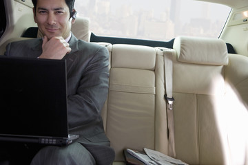 Businessman sitting in backseat of car, wearing mobile phone hands-free device, using laptop, smiling, front view, portrait (tilt)