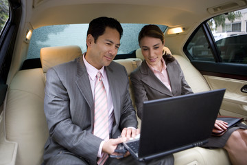 Businessman and woman sitting in backseat of car, using laptop, smiling
