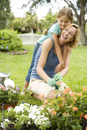 daughter hugging mother gardening