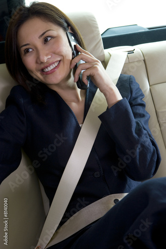 Businesswoman sitting in backseat of car, wearing seatbelt, using mobile phone, smiling, looking away