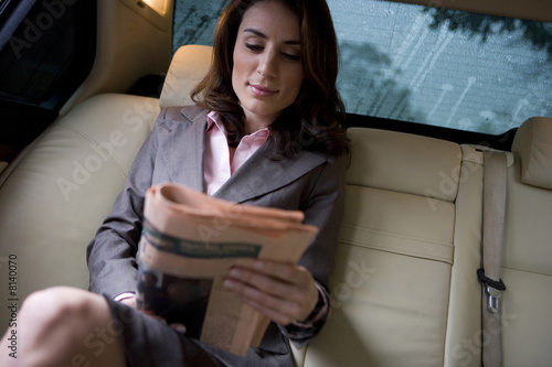 Businesswoman sitting in backseat of car, reading financial broadsheet newspaper, smiling, front view (tilt)