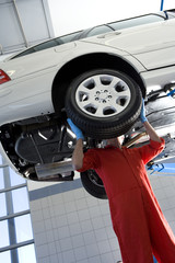 Male car mechanic, in red overalls and protective gloves, standing below car on hydraulic platform in auto repair shop, replacing wheel, face obscured (tilt)