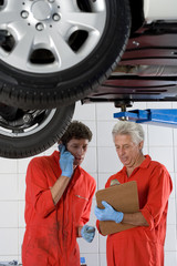 Two car mechanics, in red overalls and protective gloves, standing below car on hydraulic platform in auto repair shop, mature man holding clipboard, younger man using mobile phone
