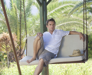 A man relaxing on a swing