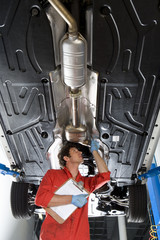 Male car mechanic, in red overalls and protective gloves, looking at underside of car on hydraulic platform in auto repair shop, holding clipboard, low angle view