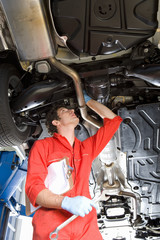 Male car mechanic, in red overalls and protective gloves, looking at underside of car on hydraulic platform in auto repair shop, holding wrench and clipboard