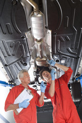 Two car mechanics, in red overalls and protective gloves, standing below car on hydraulic platform in  auto repair shop, mature man holding clipboard, younger man repairing exhaust with wrench
