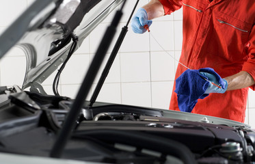 Male car mechanic, in red overalls and protective gloves, looking at car dipstick in auto repair shop, mid-section, side view