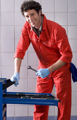 Male car mechanic, in red overalls and protective gloves, taking wrench from tool tray in auto repair shop, smiling, side view, portrait