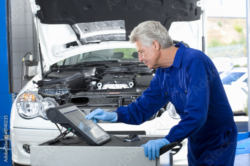 Mature car mechanic, in blue overalls, using computer in auto repair shop, profile, car with open bonnet in background