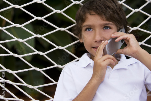 little boy talking on cell phone sitting in hammock