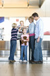 Family checking in at airport check-in desk, female check-in attendant passing boarding passes to boy (8-10), smiling, rear view