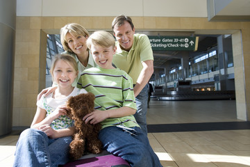 Family standing beside luggage trolley in airport, children (7-10) sitting on suitcases with soft toy, smiling, front view, portrait
