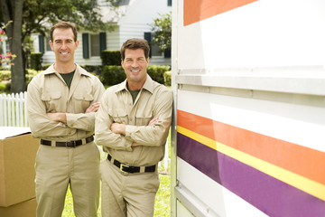 Removal men standing beside their van with packing boxes