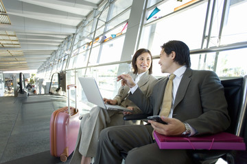 Businessman and woman sitting in airport departure lounge, using laptop, smiling, side view
