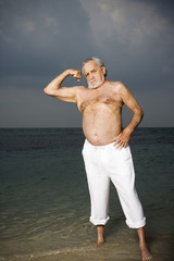 Portrait of a senior man stood in the sea flexing his biceps