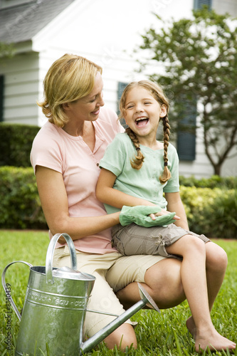 girl sitting on mother's lap laughing in the garden