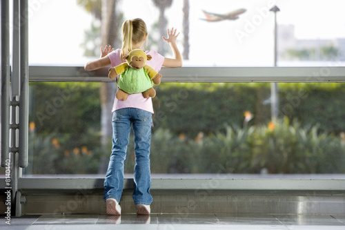 Girl (7-9), with 'monkey' rucksack, looking through large window in airport departure lounge, leaning against glass, watching aeroplane taking off, rear view