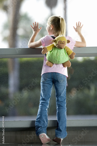 Girl (7-9), with 'monkey' rucksack, looking through large window in airport departure lounge, leaning against glass, rear view