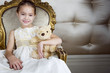 Little girl sitting in an ornate chair wearing a party dress holding a teddy bear