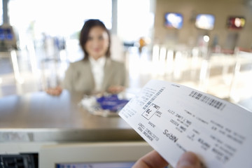 Businesswoman checking in at airport, focus on boarding pass in check-in attendant's hands in foreground, view from behind check-in desk