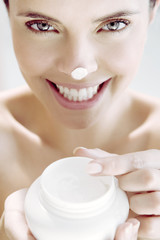 Woman holding a pot of moisturising cream, a blob on her nose