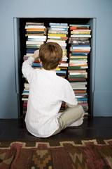 boy choosing book from bookshelf