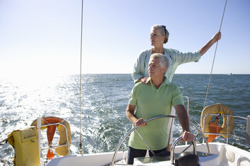 Mature couple sailing out at sea, man standing at helm of yacht, steering, woman looking at view from stern, hand on man's shoulder, front view (backlit)