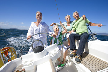 Two mature couples sailing out at sea, mature man standing at helm of yacht, steering, smiling, front view (tilt)