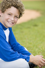 Boy with curly hair sitting on the grass