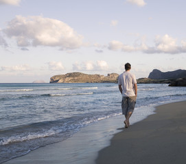 A man walking alone on a beach
