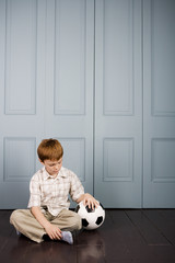 little boy sitting on the floor with football