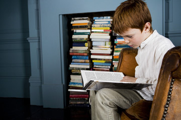 boy reading book sitting in armchair