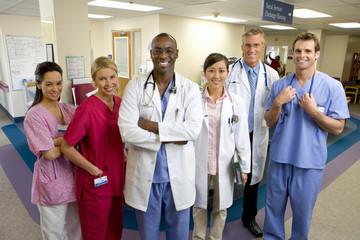 Hospital staff standing in ward, smiling, portrait
