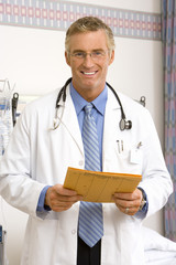 Mature male doctor with holding file, smiling, portrait