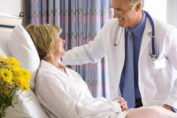 Mature male doctor smiling at mature female patient in hospital bed, side view