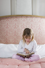 Young girl in her bedroom reading a book