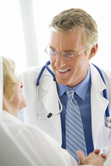 Mature male doctor smiling at mature female patient, close-up